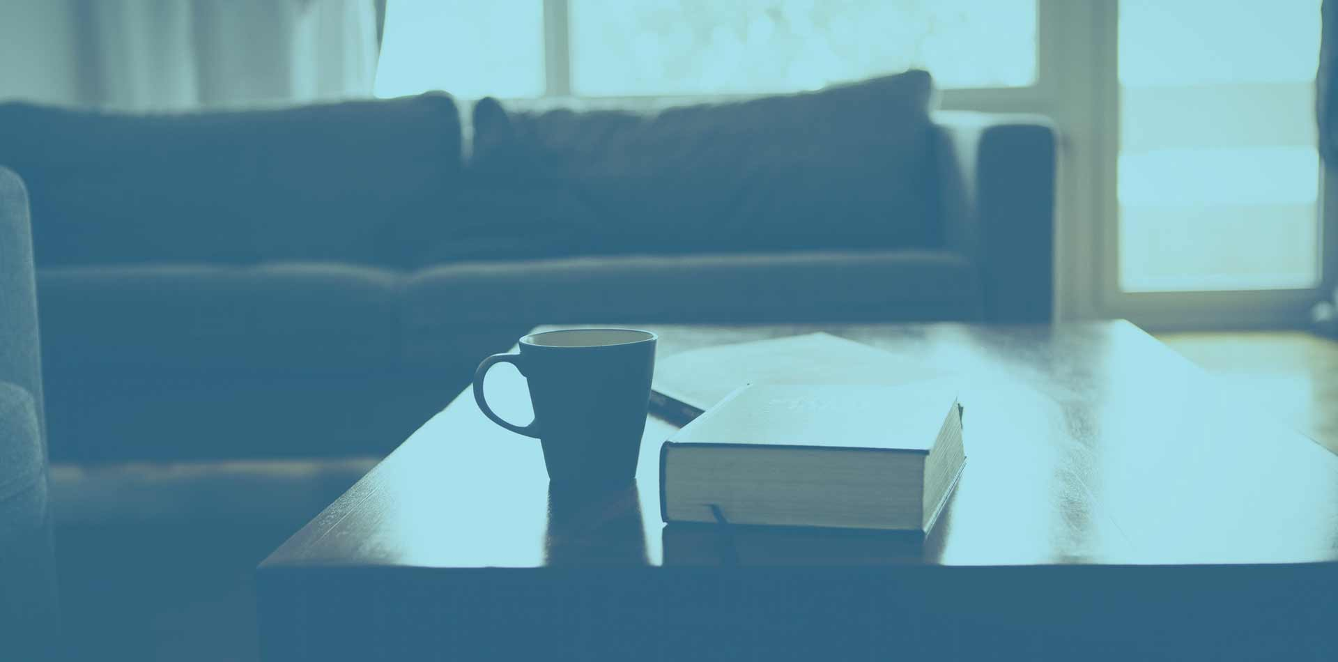 a room with a couch and a coffee table with a bible and coffee on the table